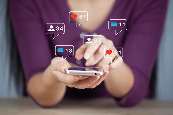 mujer recibiendo likes en su móvil por su estrategia de video en redes sociales